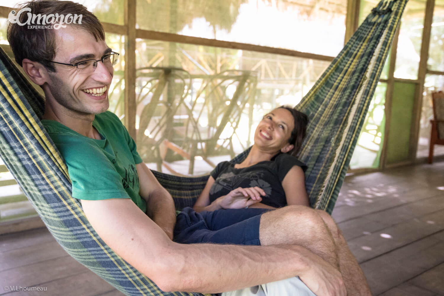 Happy couple relaxing on Amazon Experience lodge